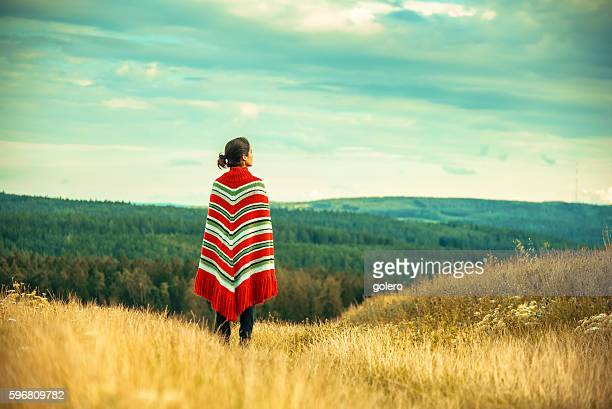 woman with poncho looking over the landscape