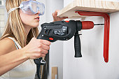Woman with power drill and eye goggles