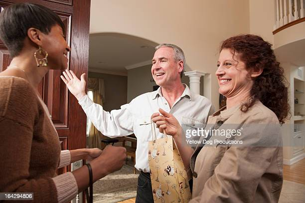 Woman with present arriving at house for a party