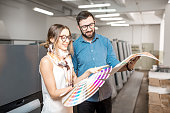 Young woman designer and print operator working together with color swatches standing at the print manufacturing