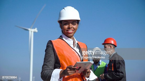 Woman with protective helmet against wind turbine : Stock Photo