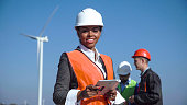 Female engineer wearing hardhat standing with digital tablet against other engineers and wind turbine on sunny day and looking at camera