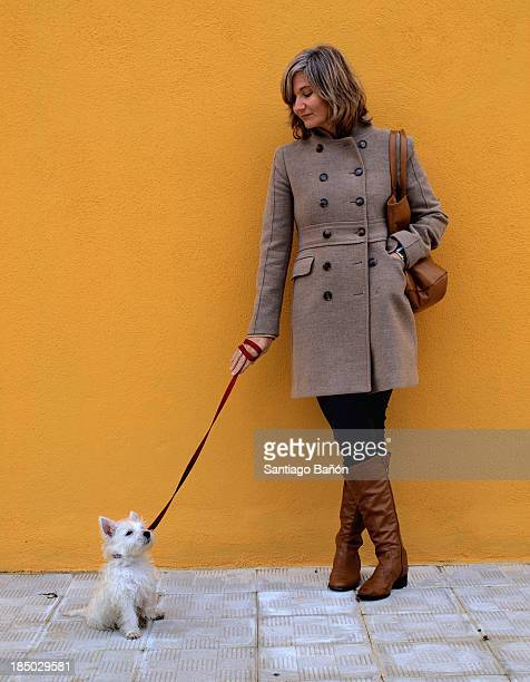 Woman with puppy in front of orange wall