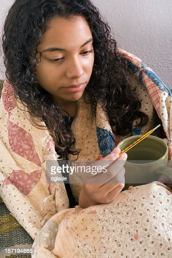 Woman with quilt over shoulders holding mug and thermometer