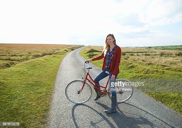 Woman with red bike on country lane.