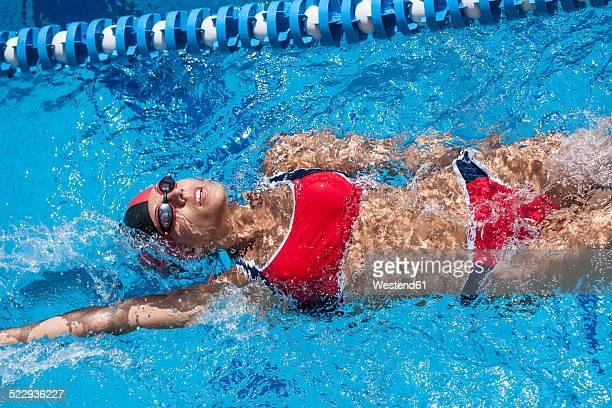 Woman with red bikini swimming in pool