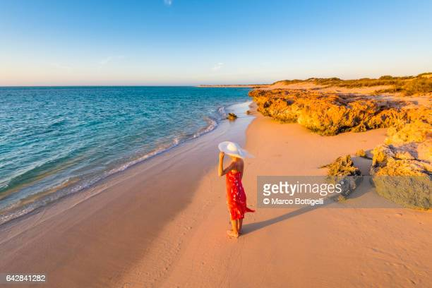 Woman with red dress on Osprey Bay beach at sunset. Western Australia.