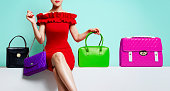 Elegant look red dress woman sitting with colourful handbags. Fashion shopping image.