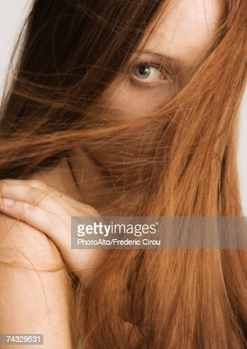 Woman with red hair covering half of face, portrait : Stock Photo