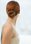 Woman with red hair in bun and strapless top, rear view
