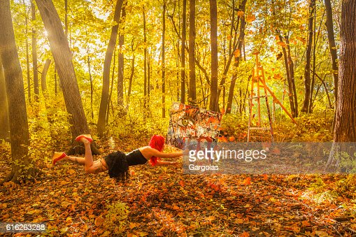 Woman with red hair levitation who painted in the forest : Stock Photo
