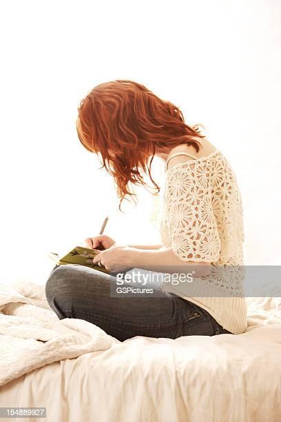 Frau mit roten Haaren im Bett sitzend Schreiben