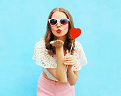 Pretty woman in sunglasses with red heart lollipop sends an air kiss over colorful blue background