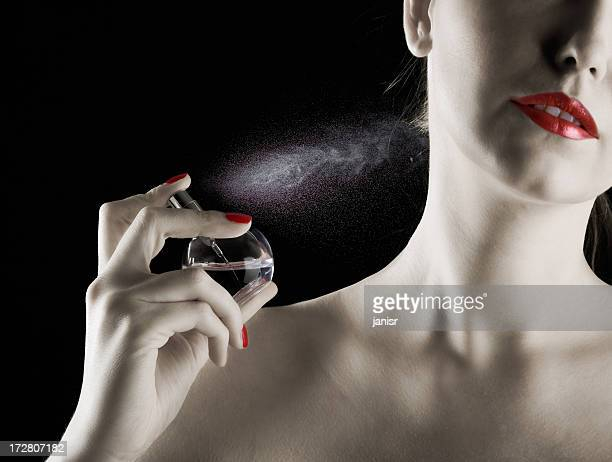 Woman with red lipstick and nails spraying perfume on neck