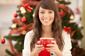 """""""Woman drinking from red mug by the christmas tree. Looking at camera.Please, see CHRISTMAS images with this FAMILY, for lightbox click the image below."""""""