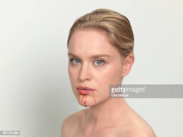 woman with red raspberry dripping from her mouth