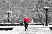 Woman with red umbrella walking through black and white landscape during noreaster snow storm in Washington Square Park, New York City
