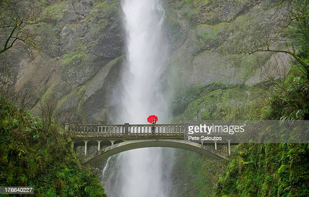 Woman with red umbrella in front of Multnomah Falls, Columbia River Gorge, USA