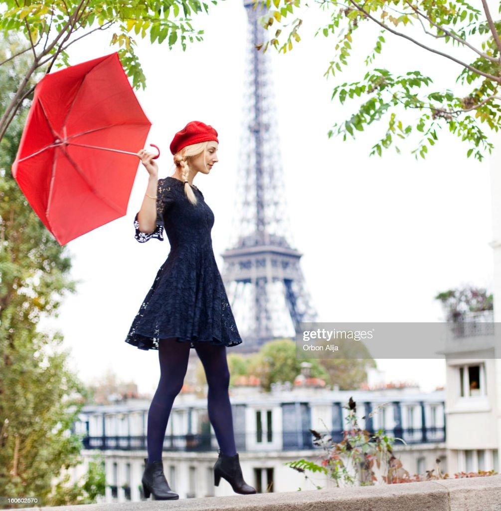 Frau mit roten Regenschirm nahe dem Eiffelturm : Stock-Foto