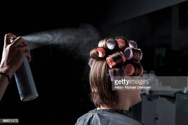 Woman with rollers getting hairsprayed
