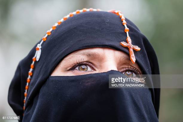 TOPSHOT A woman with rosary beads around her head attends the antigovernment proabortion demonstration in front of Polish Pariament in Warsaw Poland...