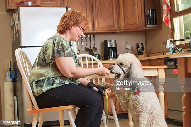 Woman with RSD feeding her service dog