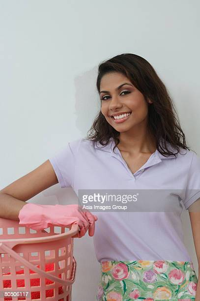 Woman with rubber gloves and washing basket, smiling at camera