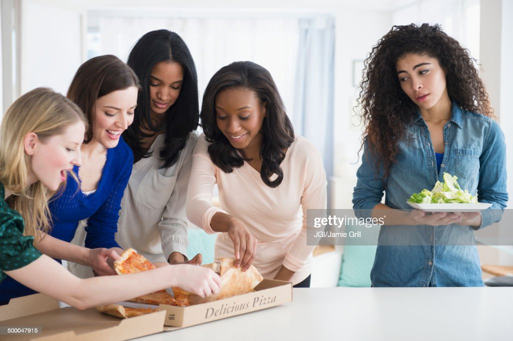 Woman with salad watching friends eat pizza