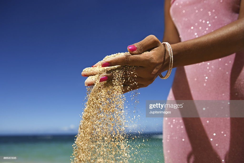 Woman with sand running through her fingers