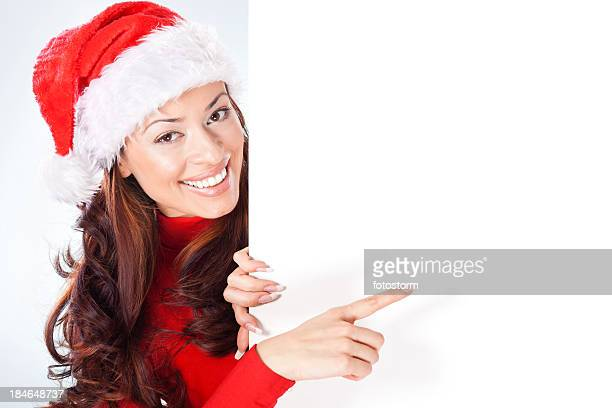 Woman with Santa hat pointing at blank banner