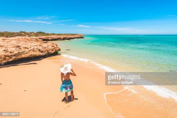 Woman with sarong and straw hat looking away on the beach at Osprey Bay, Cape Range National Park, Exmouth, Western Australia.