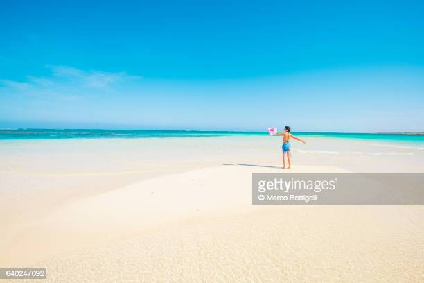Woman with sarong in pristine waters at Turquoise Bay, Ningaloo Coast, Exmouth, Western Australia.