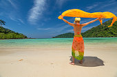 Happy and fashionable woman dressed in yellow color does fly his sarong on tropical white beach of Koh Surin Nuea, North Surin Island National Park, Phang Nga, Andaman Sea, Thailand