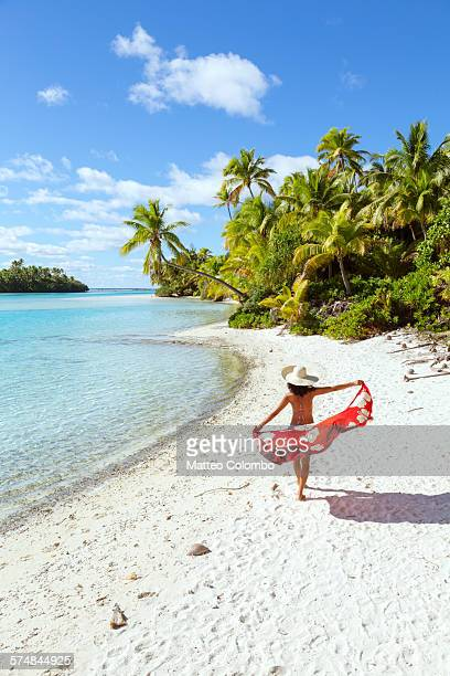 Woman with sarong walking on tropical beach