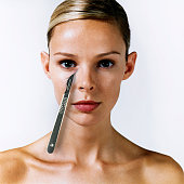 Woman with scalpel 'cutting' beneath right eye, portrait