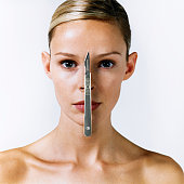 Woman with scalpel on face, portrait