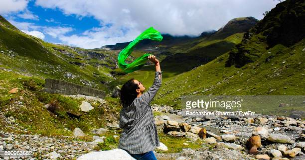 Woman With Scarf Standing On Landscape Against Sky