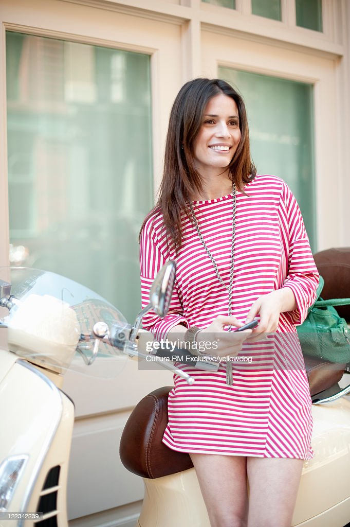 Woman with scooter on city street : Stock Photo