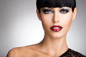 Beautiful woman with  sexy red lips and fashion color eye makeup. Closeup portrait of a female model.