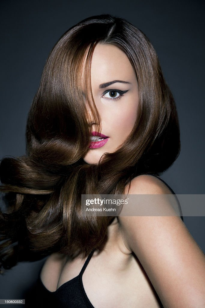 Woman with shiny wavy hair covered face. : Stock Photo