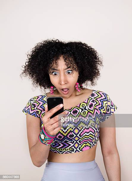 woman with shocked expression looking at phone