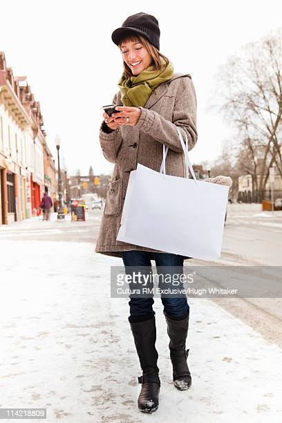 Woman with shopping bag texting