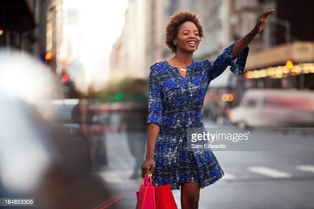 Frau mit Einkaufstaschen winkt einem taxi auf Stadt-Straße