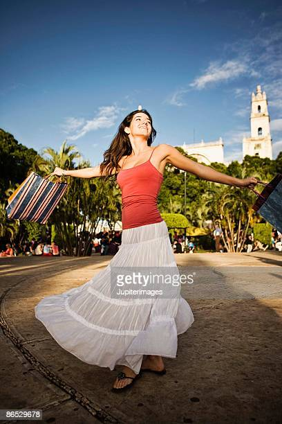 Woman with shopping bags spinning outdoors