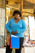 Woman with shopping bags standing outside store