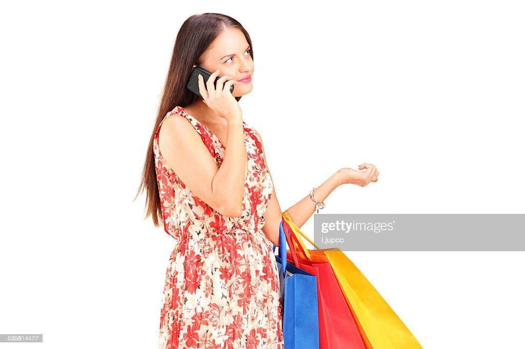 Mulher com sacos de compras, falando em um telefone : Foto de stock