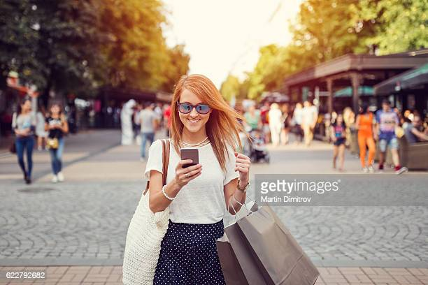 Woman with shopping bags texting in the city