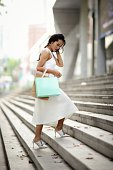 Woman with shopping bags walks up steps