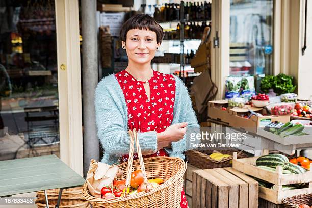 Woman with shopping basket in front of farm shop.