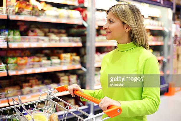 Woman with shopping trolley at a supermarket.